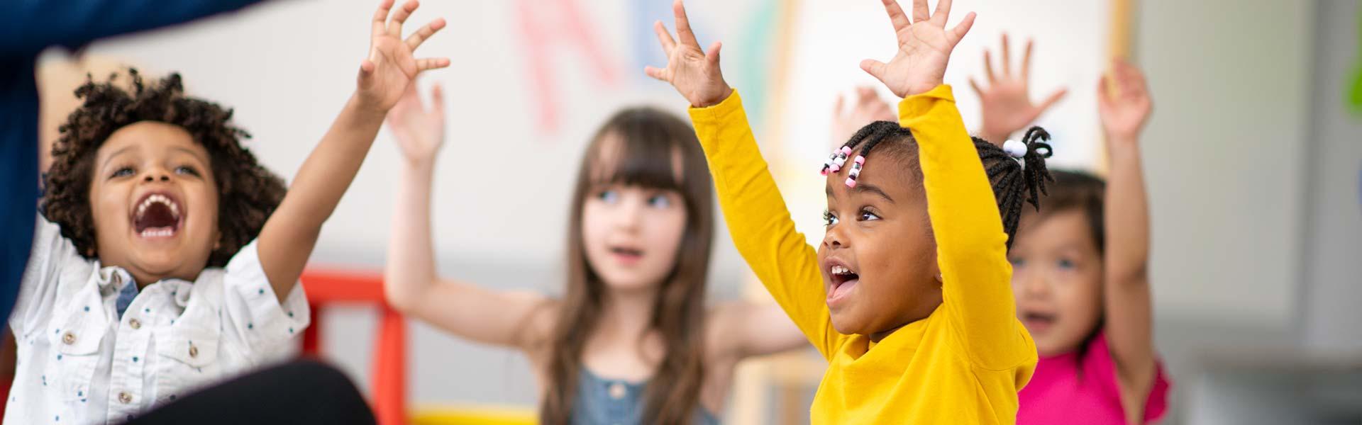 Kinder singen mit hochgestreckten Armen