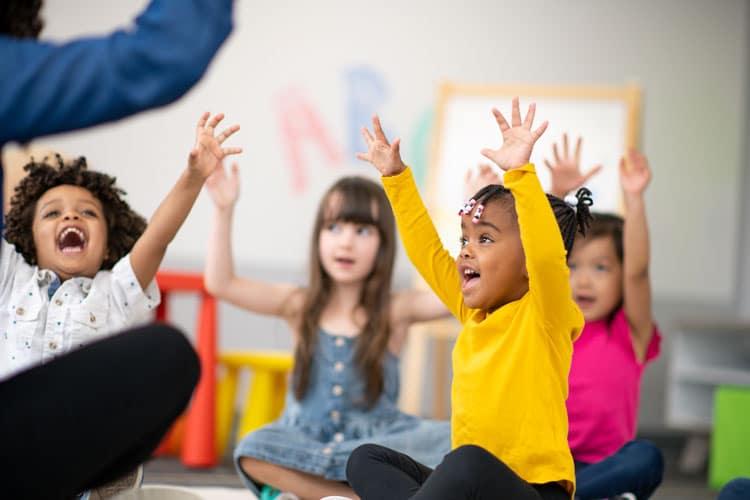 Singende Kinder mit hochgestreckten Armen